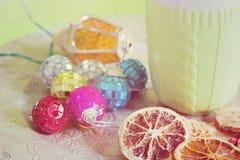 Kopp, julbollar och cuted frukter, tonat retro Arkivfoton
