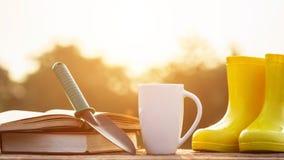 Kopp kaffe, bok och trädgårdutrustning på trätabellen med s royaltyfri fotografi