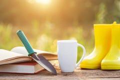 Kopp kaffe, bok och trädgårdutrustning på trätabellen med s arkivbilder