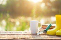 Kopp kaffe, bok och trädgårdutrustning på trätabellen med s royaltyfri bild
