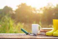 Kopp kaffe, bok och trädgårdutrustning på trätabellen med s royaltyfria foton