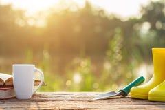 Kopp kaffe, bok och trädgårdutrustning på trätabellen med s arkivfoto
