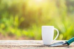 Kopp kaffe, bok och trädgårdutrustning på trätabellen med s fotografering för bildbyråer