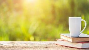 Kopp kaffe, bok och trädgårdutrustning på trätabellen med s royaltyfri foto