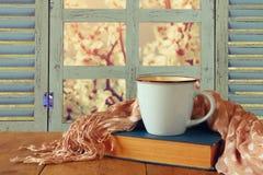 Kopp kaffe bredvid den gamla boken framme det gamla lantliga fönstret Royaltyfri Foto
