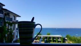 Kopp kaffe bredvid havet royaltyfria foton