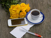 Kopp kaffe bukett av gula rosor, telefon, handtaget, ten Arkivbilder