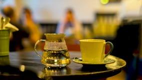 Kopp kaffe eller utslagsplats, glass tekanna av varmvatten, morgon Avbilda med suddiga kafébesökare i en låg tangent, för bakgrun royaltyfri fotografi
