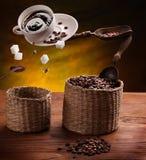 Kopp kaffe, ett socker och kaffebönor i luften. arkivfoto
