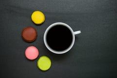 Kopp kaffe för bästa sikt och fransmanmacaron på svart bakgrund arkivbild