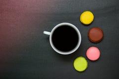 Kopp kaffe för bästa sikt och fransmanmacaron på svart bakgrund arkivbilder