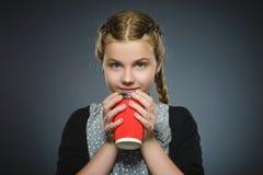 Kopp kaffe för drink för tonårs- flicka som röd isoleras på grå bakgrund arkivbilder