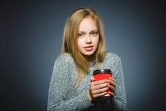 Kopp kaffe för drink för tonårs- flicka som röd isoleras på grå bakgrund arkivfoto