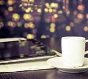 Kopp kaffe framme av den digitala minnestavlaPC:n nära fönster, tappningstil royaltyfria bilder