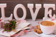 Kopp kaffe, gåvor, blommor och ordförälskelse på träbakgrund Underbar morgon på dag för valentin` s royaltyfri foto