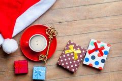 Kopp kaffe, gåvor, guld- tangent och Santa Claus hatt på wonden Royaltyfri Foto