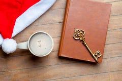 Kopp kaffe, guld- tangent, bok och Santa Claus hatt på wonden Fotografering för Bildbyråer