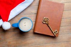 Kopp kaffe, guld- tangent, bok och Santa Claus hatt på wonden Arkivbilder