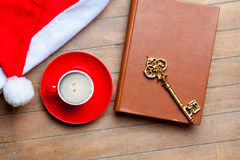 Kopp kaffe, guld- tangent, bok och Santa Claus hatt på wonden Arkivbild