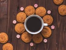 Kopp kaffe, havremjölkakor och godis på träbakgrund till arkivfoton