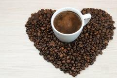 Kopp kaffe hjärta för kaffebönor på trätabellen Top beskådar klart bruk för bakgrundskaffe Royaltyfri Foto