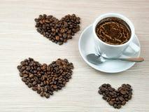Kopp kaffe hjärtor för kaffebönor Arkivbild