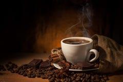 Kopp kaffe i kaffebönor på brun bakgrund Arkivfoto