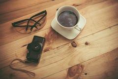 Kopp kaffe, kamera och monokel arkivfoto