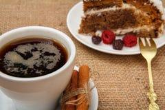 Kopp kaffe, kanel, gaffel och skiva av den ljusbruna kakan som dekoreras med piskade kräm och hallon arkivbilder