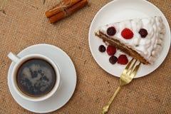 Kopp kaffe, kanel, gaffel och skiva av den ljusbruna kakan som dekoreras med piskade kr?m och hallon arkivbild