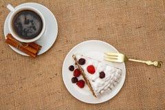 Kopp kaffe, kanel, gaffel och skiva av den ljusbruna kakan som dekoreras med piskade kr?m och hallon royaltyfria bilder