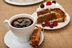 Kopp kaffe, kanel och skiva av den ljusbruna kakan som dekoreras med piskade kräm och hallon arkivfoto
