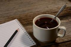 Kopp kaffe med anteckningsboken Arkivbild