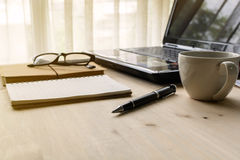Kopp kaffe med bärbara datorn på träskrivbordet och bunt av dokumentet Arkivbild