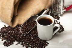 Kopp kaffe med bönor och en fransk press Arkivfoton