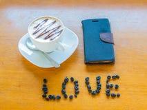 Kopp kaffe med bönor och mobilen Arkivbilder