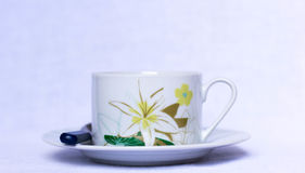 Kopp kaffe med blom- detaljer på en platta Arkivfoto