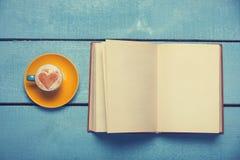 Kopp kaffe med boken Arkivfoto