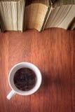 Kopp kaffe med bunten av gamla böcker arkivfoton