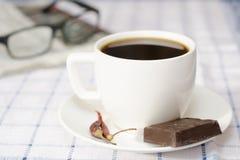 Kopp kaffe med chili och choklad, exponeringsglas och tidning arkivbild