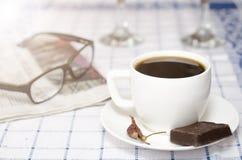 Kopp kaffe med chili och choklad, exponeringsglas och tidning Fotografering för Bildbyråer