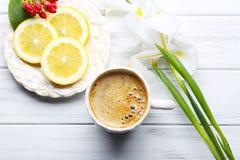 Kopp kaffe med citronskivor och härliga blommor på trä fotografering för bildbyråer