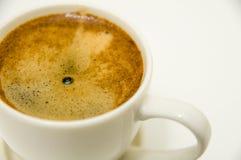Kopp kaffe med den Crema closeupen som isoleras på vit Arkivbild