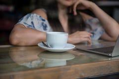 Kopp kaffe med den funktionsdugliga kvinnan och hennes bärbar dator Arkivbild