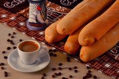 Kopp kaffe med den kaffebönor och bagetten royaltyfri bild