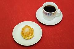 Kopp kaffe med den kräm- puffen Arkivfoto