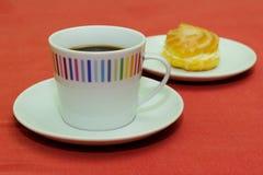 Kopp kaffe med den kräm- puffen Royaltyfria Foton