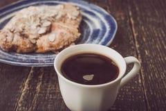 Kopp kaffe med den suddiga gifflet med mandeln på den blåa keramiska plattan Arkivbilder