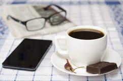 Kopp kaffe med den telefonexponeringsglas och tidningen Fotografering för Bildbyråer