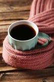 Kopp kaffe med den varma halsduken på den bruna träbakgrunden Arkivbilder